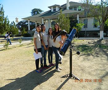 Uno de los 27 clubes de astronomía que participaron en el Programa Del Aula al Universo en la región de Cananea, Sonora, haciendo prácticas de observación solar. Al fondo, la Casa Greene, sede del Observatorio Astrofísico Guillermo Haro