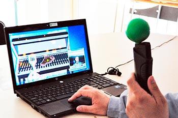 En la imagen se observa a una persona interactuando con Gesture Therapy, con la manija en su mano, la cual tiene una esfera para el seguimiento visual. En la pantalla se observa uno de los juegos —asar la carne—, y en la ventana pequeña se ilustra la detección de la esfera y el usuario por el sistema
